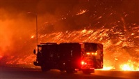 Two California wildfires destroy homes near Los Angeles, leaving at least one dead